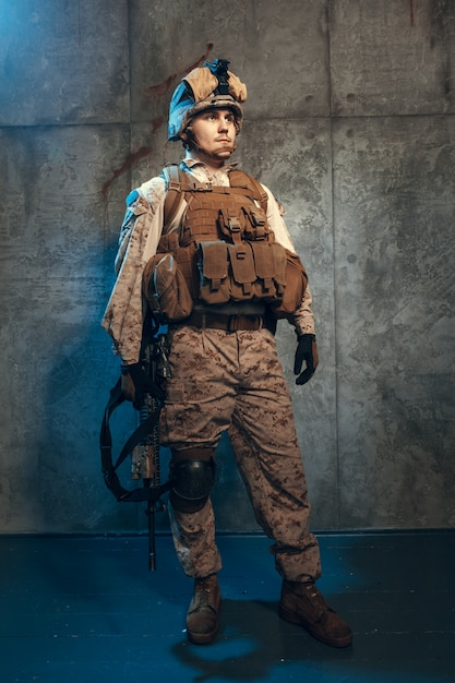 Young man in military outfit a mercenary soldier in modern times on dark Premium Photo