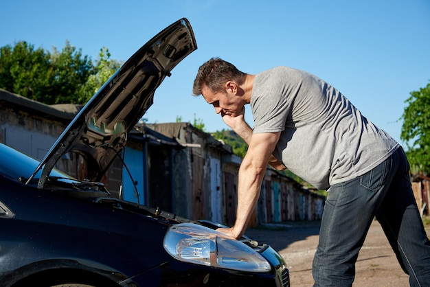 A young man near the auto with an open hood. Premium Photo