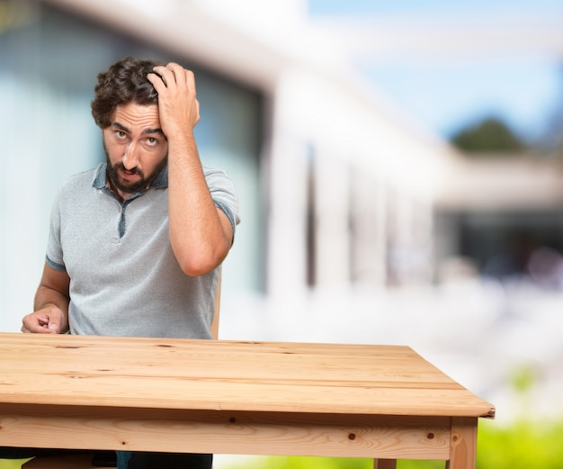 young man on a table. worried expression Free Photo