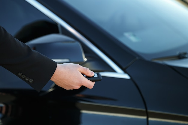 Young man opening his car door with the control remote key ...