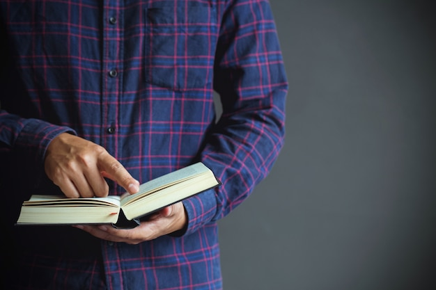 Young man opening and reading a book, copy space,close up Premium Photo
