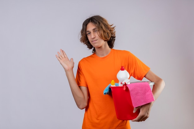 Giovane uomo in maglietta arancione tenendo la benna con strumenti di pulizia guardando fiducioso sorridente in piedi con il braccio alzato su sfondo bianco Foto Gratuite