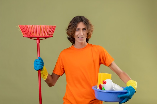 Giovane uomo in maglietta arancione che indossa guanti di gomma che tiene bacino con strumenti di pulizia e mop guardando la telecamera confuso e incerto in piedi su sfondo verde Foto Gratuite