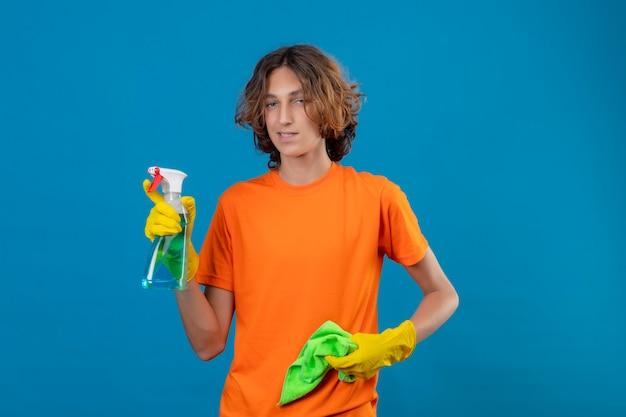 Giovane uomo in maglietta arancione che indossa guanti di gomma tenendo spray per la pulizia e rug guardando la telecamera con un sorriso fiducioso pronto per pulire in piedi su sfondo blu Foto Gratuite