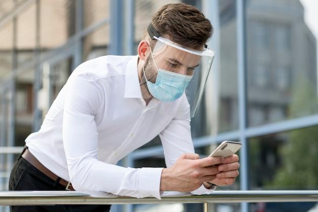 Giovane uomo all'aperto con maschera di controllo mobile Foto Gratuite