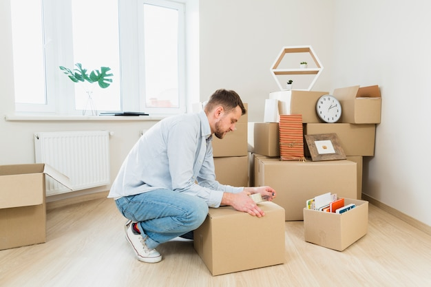 Young man packing the cardboard boxes at home Free Photo