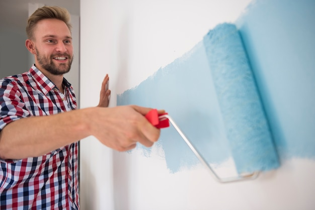 Young man painting a blue wall Free Photo