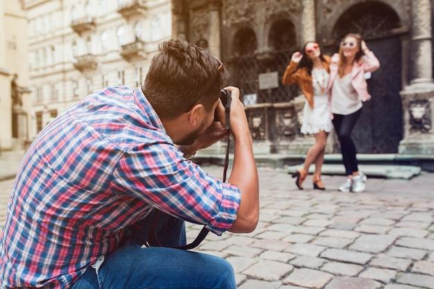 Молодой человек фотограф снимает, фотографирует с цифровой камерой своим друзьям Бесплатные Фотографии