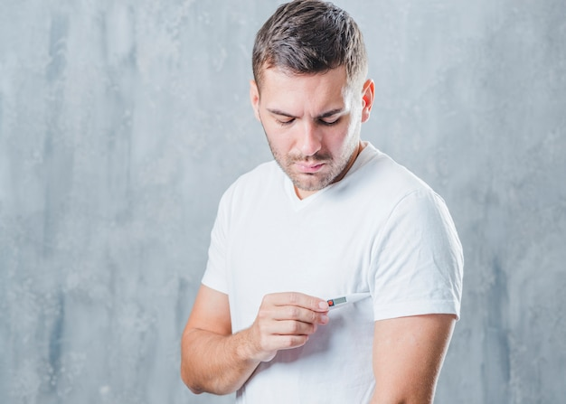 young man placing the medical digital thermometer in his under
