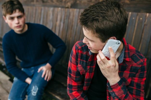 Giovane uomo in una camicia a quadri parlando sullo smartphone Foto Gratuite