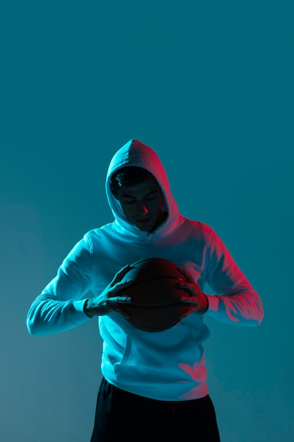 Молодой человек играет в баскетбол наедине с холодными огнями Бесплатные Фотографии