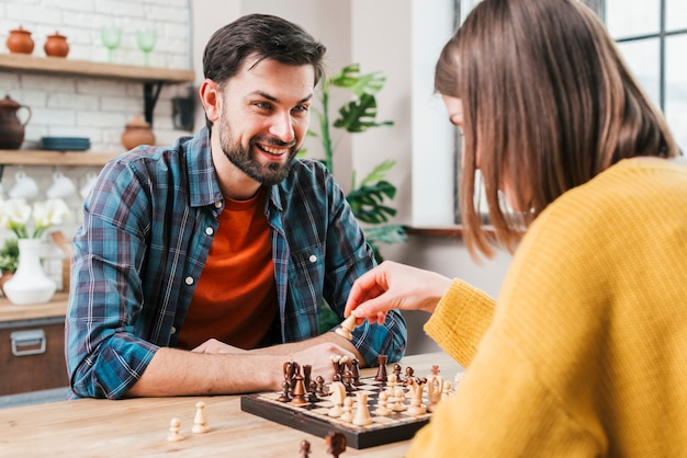 Young man playing chess with his wife at home Free Photo