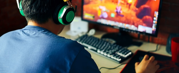Young man playing game on computer, banner Premium Photo