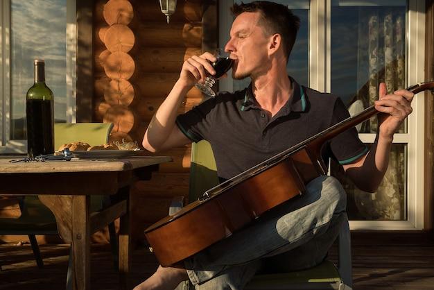 기타 연주와 혼자 와인을 마시는 젊은 남자. 코로나 19 건강 격리. 프리미엄 사진