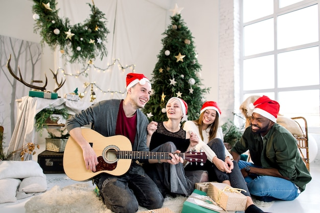 Young man playing guitar and friends are smiling and singing sitting near christmas tree Premium Photo