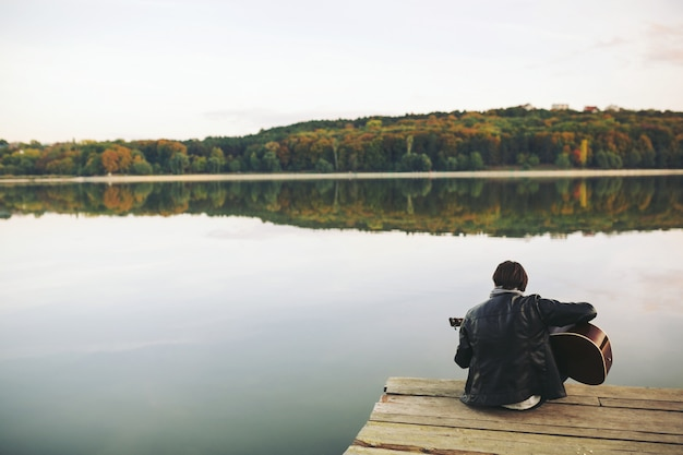 Young man playing on guitar at the lake Free Photo