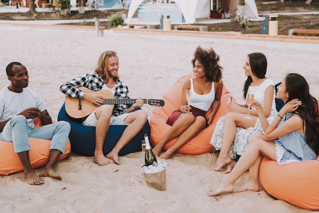 Young man playing guitar for multiracial friends. Premium Photo