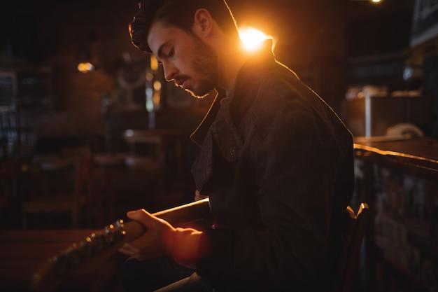Молодой человек играет на гитаре Premium Фотографии