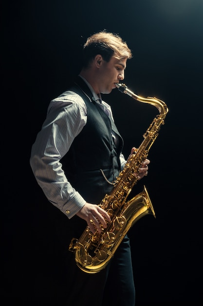 Young man playing the saxophone Premium Photo