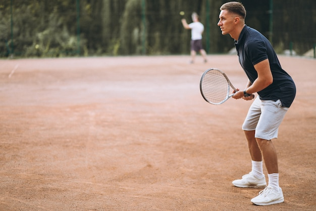 Young man playing tennis at the court Free Photo
