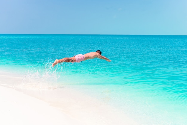 Young man plunging into the turquoise sea Premium Photo