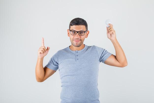 Молодой человек указывая пальцем вверх и держа лампочку в серой футболке, вид спереди очки. Бесплатные Фотографии