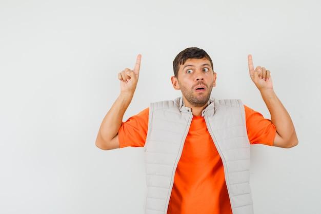 若い男はtシャツ、ジャケットで指を上に向けて怖がって見える 無料写真