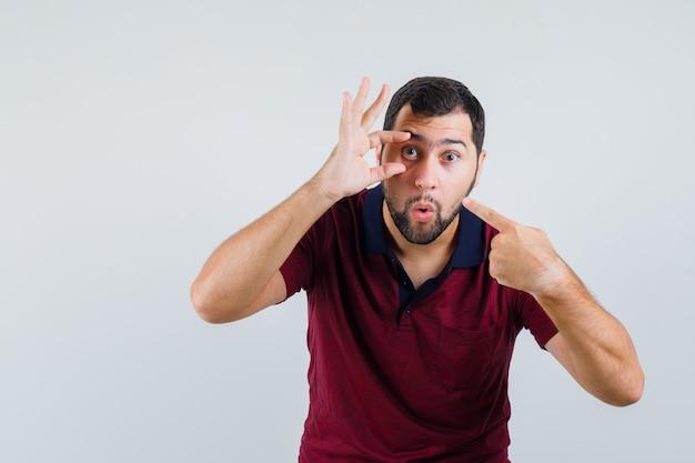 Giovane uomo che punta alla palpebra in maglietta rossa e guardando concentrato. vista frontale. Foto Gratuite