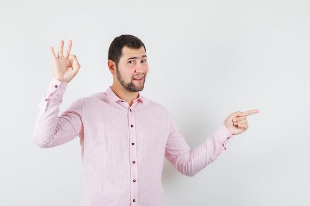 Молодой человек, указывая в сторону со знаком ок в розовой рубашке и выглядит уверенно Бесплатные Фотографии