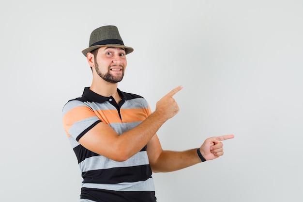 Tシャツ、帽子、楽観的に見える側を指している若い男。 無料写真