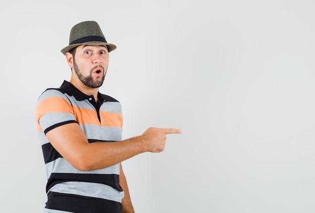 Tシャツ、帽子、不思議に見える側を指している若い男 無料写真