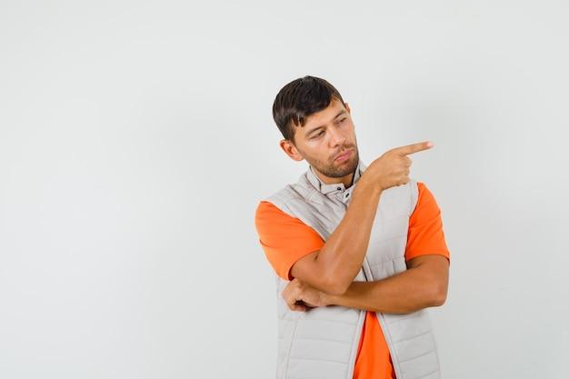 Tシャツ、ジャケットで横を指して、賢明に見える若い男。 無料写真