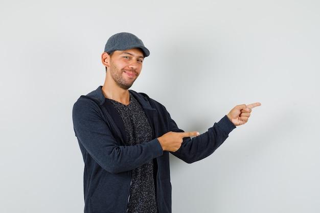 若い男は、tシャツ、ジャケット、キャップで横を指して、楽観的に見えます。 無料写真
