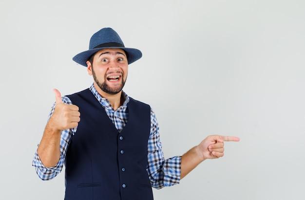若い男が横を指して、シャツ、ベスト、帽子に親指を立てて、嬉しそうに見える 無料写真
