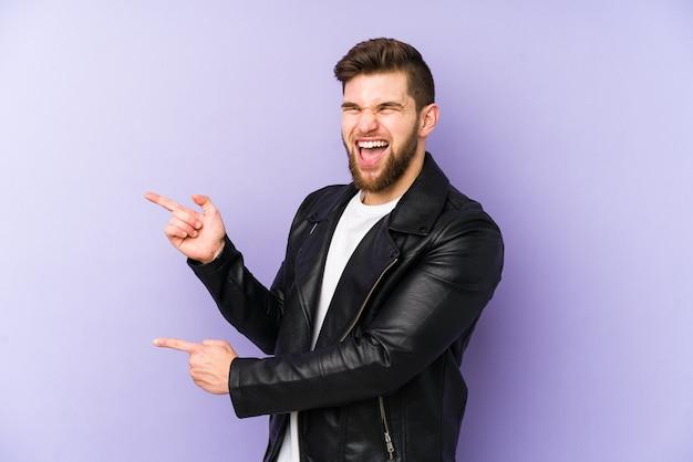 Молодой человек, указывая указательными пальцами на место для копирования, выражает волнение и желание. Premium Фотографии
