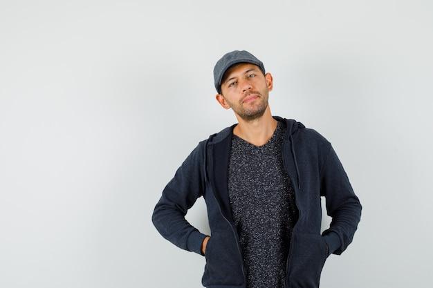 T- 셔츠, 재킷, 모자에 주머니에 손을 포즈와 우아한 찾고 젊은 남자. 무료 사진