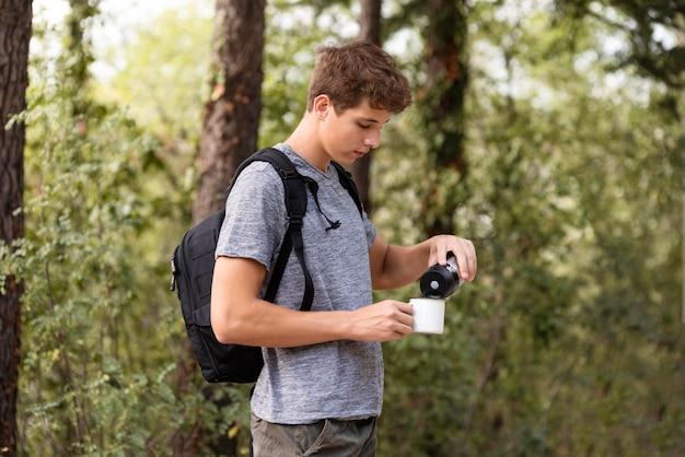 Молодой человек наливает напиток в чашку Premium Фотографии