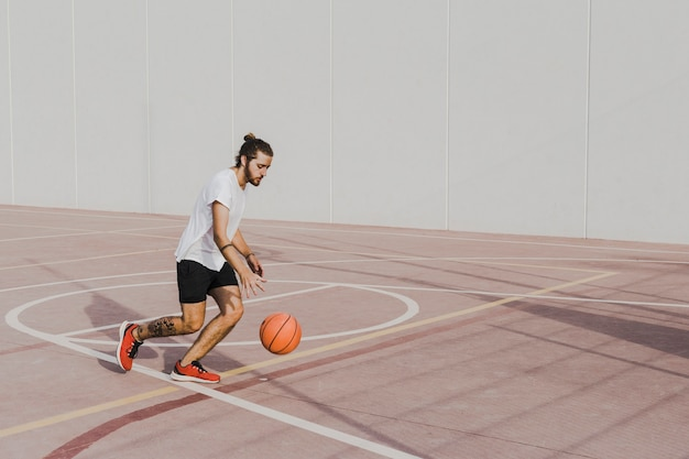 Young man practicing basketball in outdoors court Free Photo