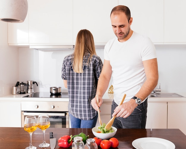 Young man preparing the salad and her wife standing behind him cooking food in the kitchen Free Photo