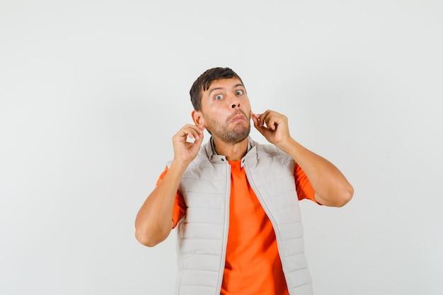 Giovane che tira giù i lobi delle orecchie in maglietta, giacca e sembra confuso Foto Gratuite