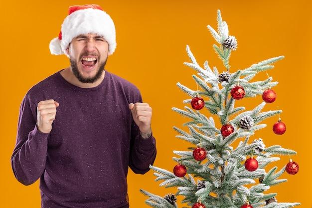 Giovane uomo in maglione viola e cappello da babbo natale stringendo i pugni gridando con espressione aggressiva in piedi accanto all'albero di natale su sfondo arancione Foto Gratuite