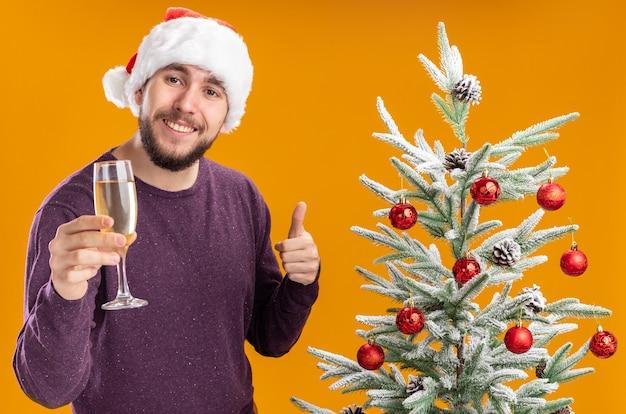 Giovane uomo in maglione viola e cappello santa tenendo un bicchiere di champagne accanto all'albero di natale su sfondo arancione Foto Gratuite