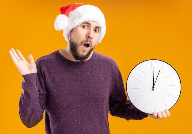 Giovane uomo in maglione viola e cappello da babbo natale che tiene orologio da parete confuso e molto ansioso scrollare le spalle in piedi sopra la parete arancione Foto Gratuite