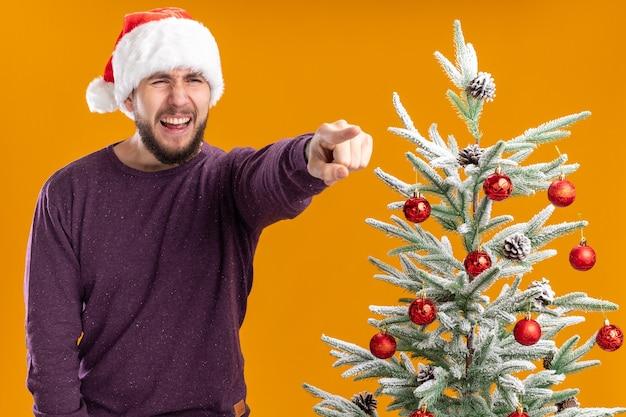 Giovane uomo in maglione viola e santa hat guardando a parte con espressione infastidita che punta con il dito indice a qualcosa in piedi accanto all'albero di natale su sfondo arancione Foto Gratuite