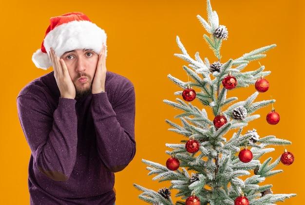 Giovane uomo in maglione viola e cappello da babbo natale che guarda l'obbiettivo confuso e molto ansioso accanto all'albero di natale su sfondo arancione Foto Gratuite