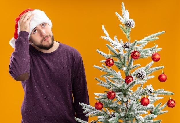 Giovane uomo in maglione viola e cappello santa cercando confuso e molto ansioso in piedi accanto all'albero di natale su sfondo arancione Foto Gratuite