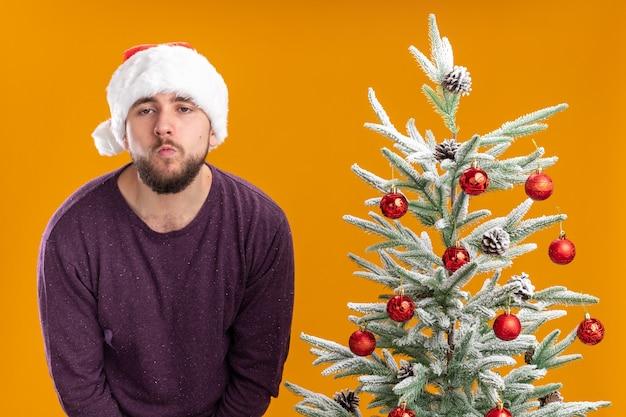 Giovane uomo in maglione viola e cappello santa cercando stanco e annoiato in piedi accanto all'albero di natale su sfondo arancione Foto Gratuite