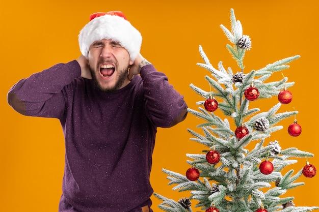 Giovane uomo in maglione viola e cappello da babbo natale che grida con espressione infastidita in piedi accanto all'albero di natale su sfondo arancione Foto Gratuite