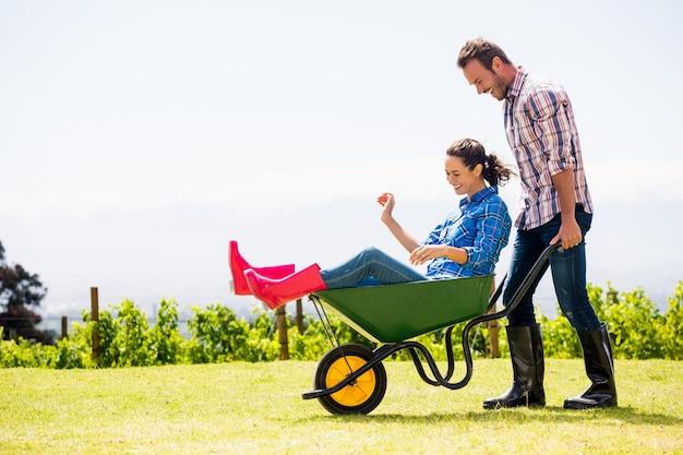 Young man pushing woman sitting in wheelbarrow Premium Photo