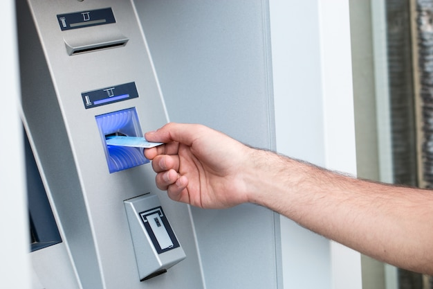 Young man put his credit card at the atm Premium Photo